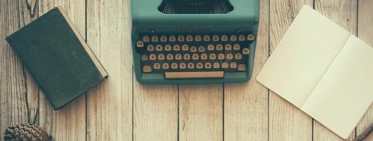 Foto com um caderno fechado, uma máquina de escrever e um caderno aberto sobre uma mesa de madeira.