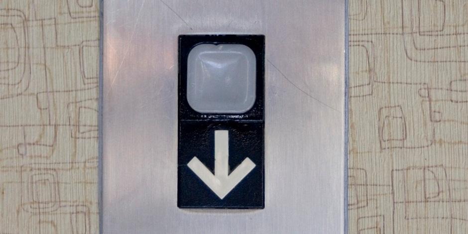 Botão de elevador. Abaixo do botão, está um ícone indicando para baixo, ou seja, o elevador só pode descer.
