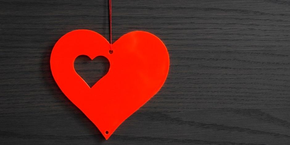 A imagem mostra um coração de papel vermelho sobre uma superfície de madeira cinzenta.