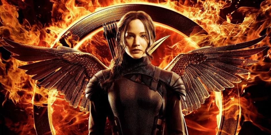 Katniss Everdeen, protagonista do livro e filme Jogos Vorazes, aparece na imagem com uma roupa especial de combate, flexível e protetora ao mesmo tempo. Ela tem uma aljava com flechas nas costas e um par de asas aparece por trás, fazendo referência ao tordo, símbolo dela. Ao redor dela, tudo é fogo.