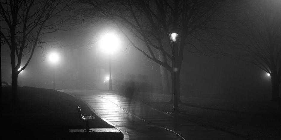Caminho em meio a um parque. É noite e as luzes das lamparinas na borda do caminho estão acesas. Existe um ou dois vultos percorrendo o caminho, suas sombras mescladas por causa das luzes.
