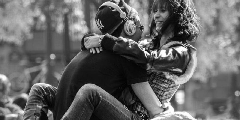 Um homem e uma mulher estão sentados e entrelaçados em um parque um de frente ao outro. Os dois riem e parecem apaixonados,