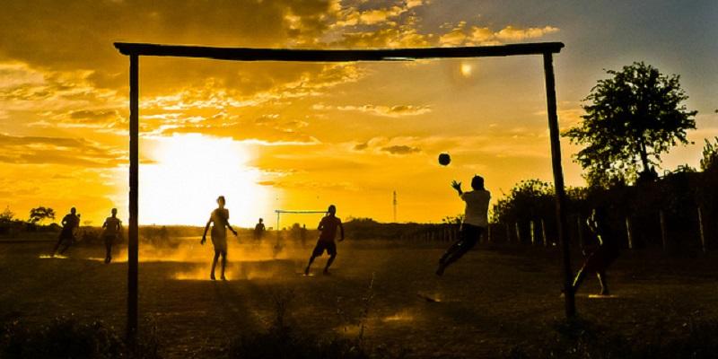 Fotografia de um campo de várzea. Algumas pessoas jogam futebol ao entardecer em um campo de terra e grama. O observador está posicionado atrás de um dos gols feitos de pedaços de madeira, onde é possível ver o goleiro pulando para defender uma bola.