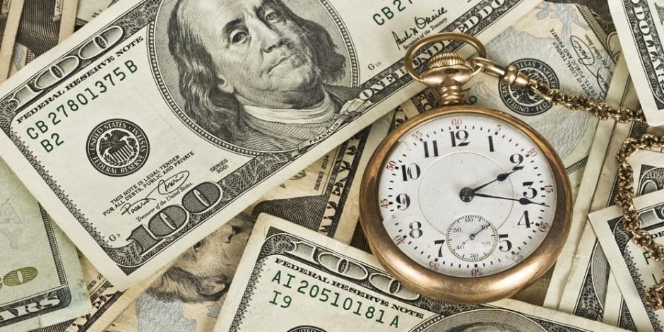 Um relógio de bolso sobre várias notas de dólares espalhadas de qualquer forma.