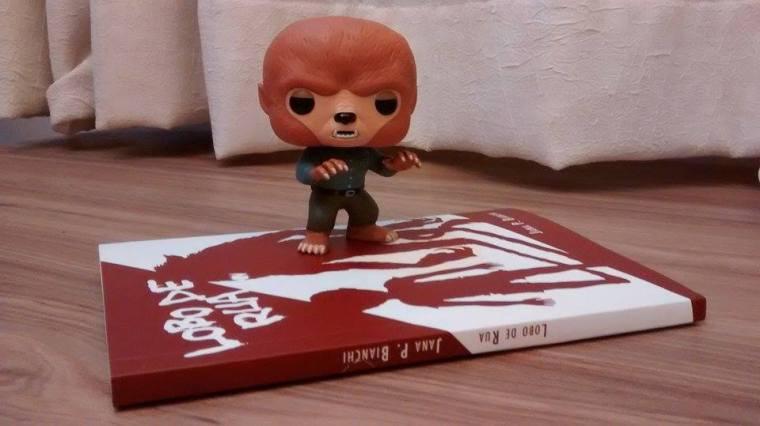 """O livro """"Lobo de Rua"""" está deitado em cima do piso de chão de madeira. Sobre ele, está um bonequinho de plástico em forma de lobisomem."""