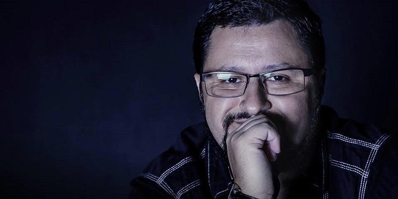 Foto do escritor Fábio M. Barreto. Ele está à frente de um fundo neutro. Só a cabeça e os ombros aparecem. Ele olha para frente, sorrindo, enquanto a mão está apoiada sobre a boca.