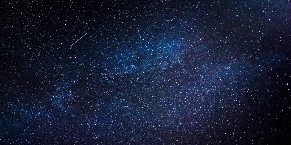 Uma noite escura e um céu cheio de estrelas. Em um ponto é possível ver uma estrela cadente.