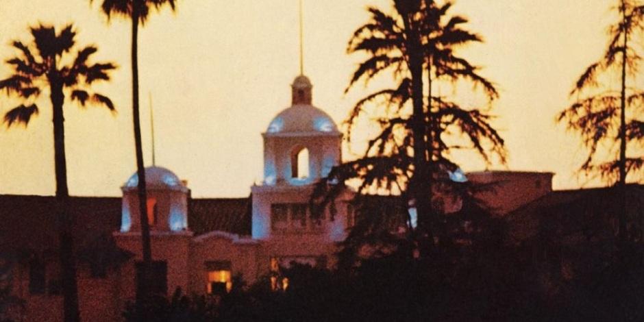 A fachada de um hotel contra o nascer do sol em um lugar cheio de árvores.