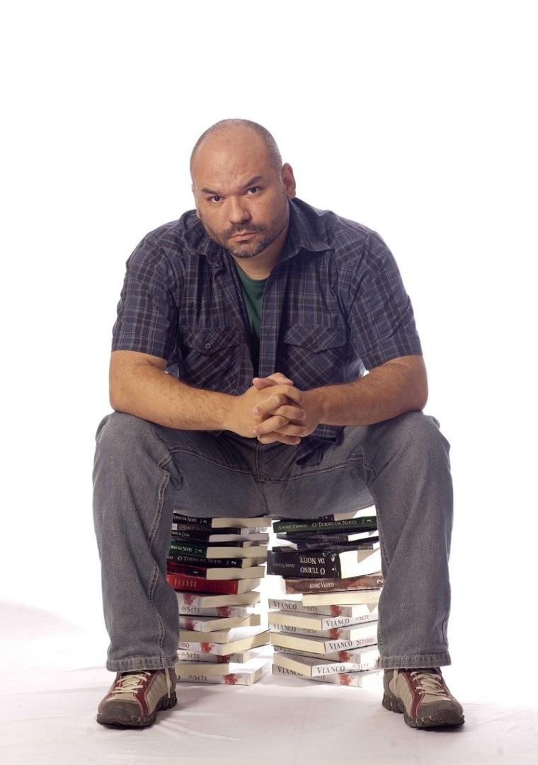 André Vianco sentado sobre uma pilha de livros escritos por ele.