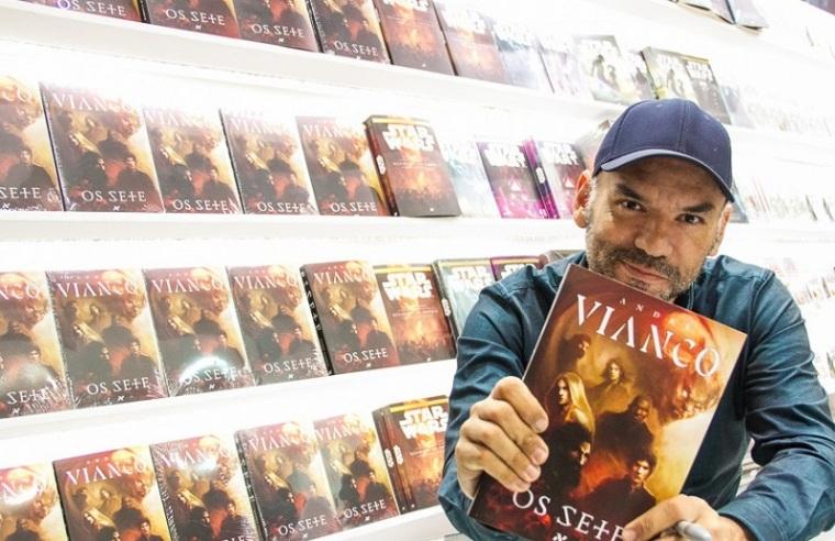 """Escritor André Vianco segurando o livro """"Os Sete"""", escrito por ele"""