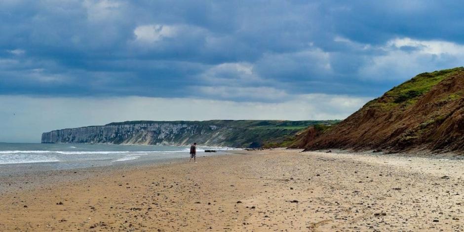 Uma praia deserta onde apenas um homem caminha. Ao seu lado esquerdo, o mar. Ao lado direito e à frente, baixas montanhas.