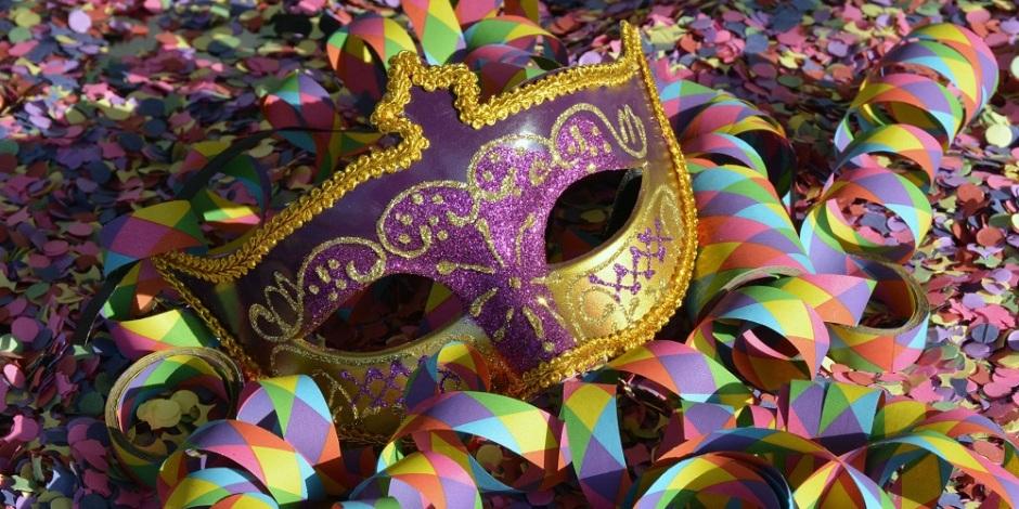 Uma máscara roxa e dourada de carnaval, apenas para tampar os olhos, em cima de uma pilha de confete e serpentina coloridos.