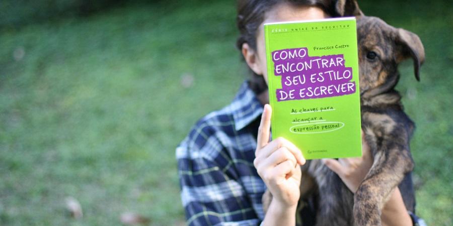Uma menina sentada na grama segura o livro 'Como encontrar seu estilo de escrever' com a mão direita. O livro tampa o rosto dela. Com a mão esquerda, ela também segura um cachorro, que tem o rosto parcialmente tampado pelo livro.